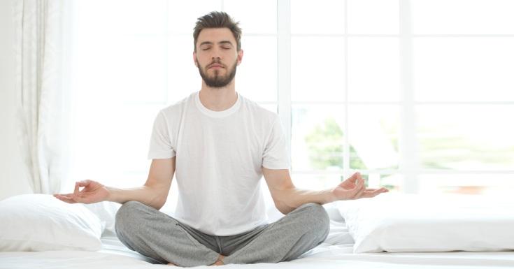 Young Man Meditating Bedroom